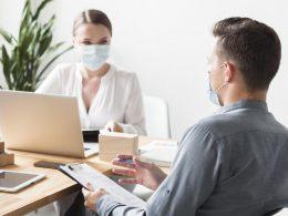 Collaborateurs en réunion, masqués et à distance